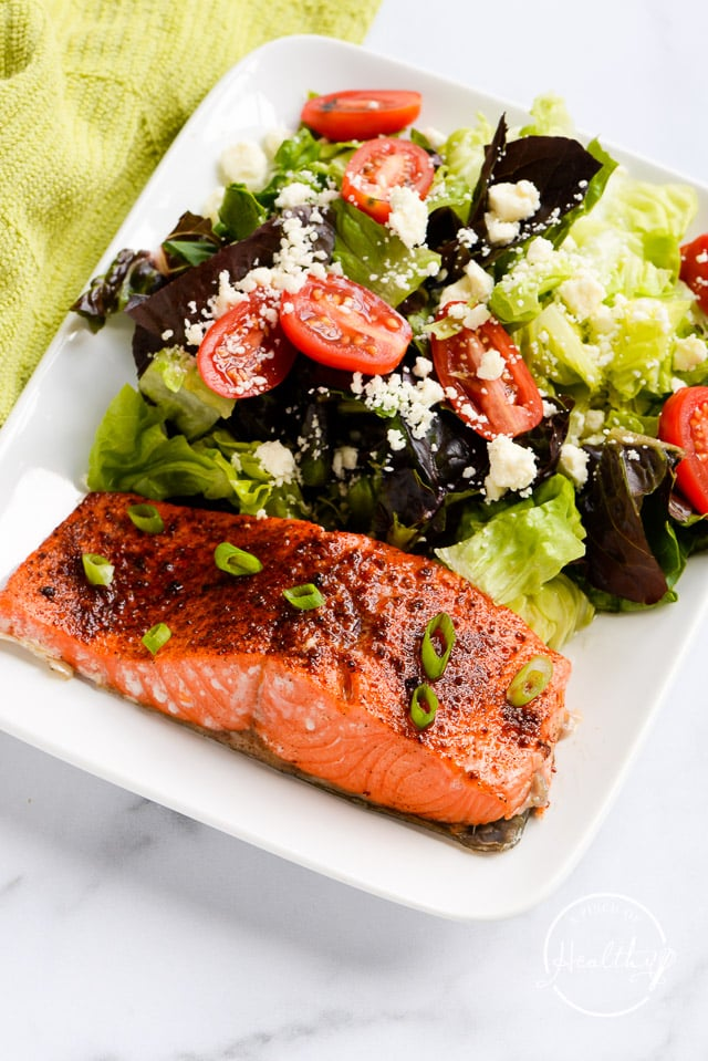 Salmon topped with thin sliced green onion on a white plate with Greek salad