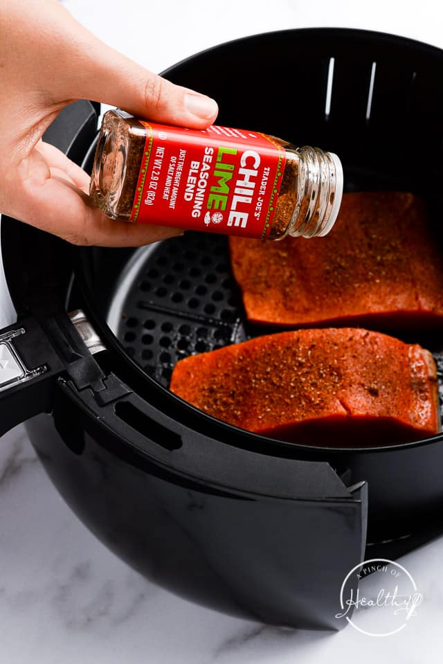 sprinkling chili lime seasoning blend on salmon in air fryer basket