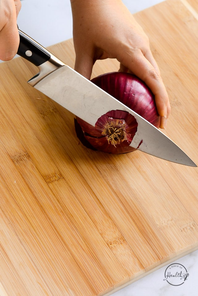 cutting stem end off red onion