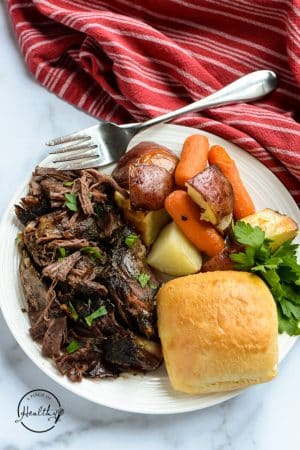 crock pot roast on a white plate with potatoes and carrots
