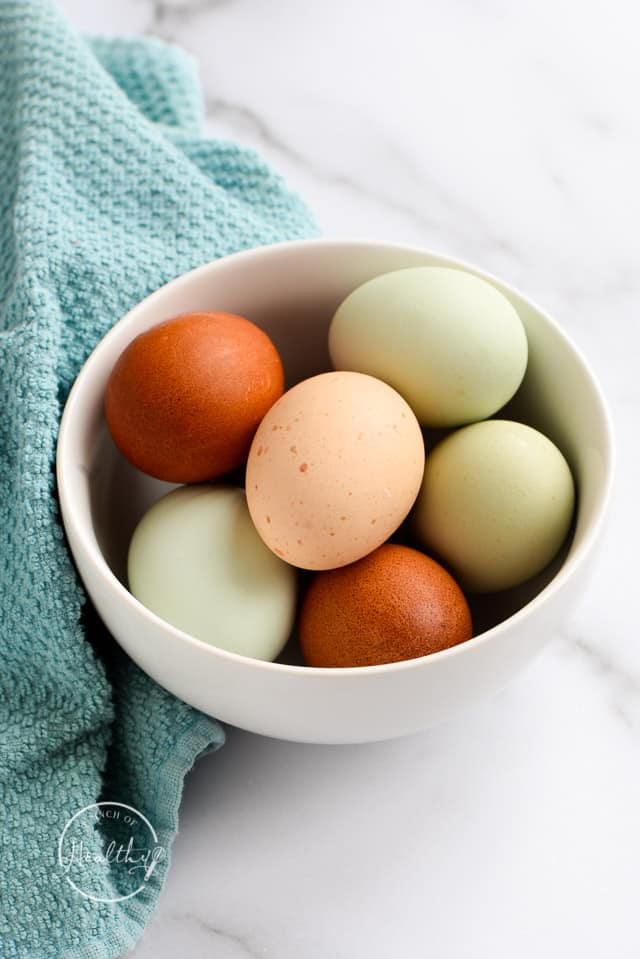 multi colored eggs in a white bowl with blue towel