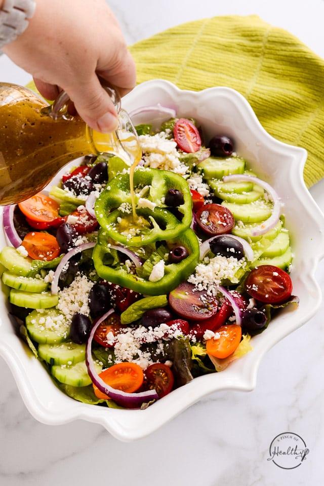 Pouring dressing on Greek salad