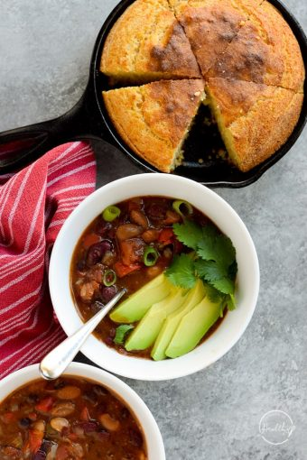 Instant pot vegetarian chili with avocado slices and cornbread