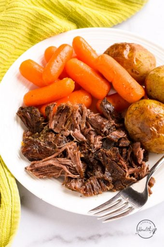 Instant Pot pot roast with carrots and potato on white plate with fork