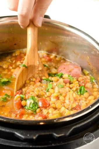 Wooden spoon stirring lentil soup in the Instant Pot