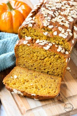 Vegan pumpkin bread, sliced and topped with oats on a wood cutting board