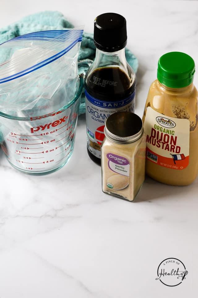 garlic powder, Tamari and dijon mjustard next to glass pyrex measuring cup lined with freezer bag