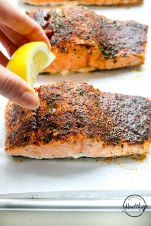 hand squeezing lemon on oven baked salmon