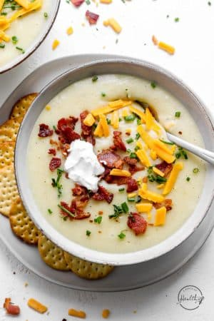 Creamy potato soup in a white bowl with bacon, sour cream and cheese