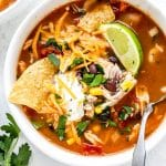 Slow cooker chicken tortilla soup in white bowl with corn chips