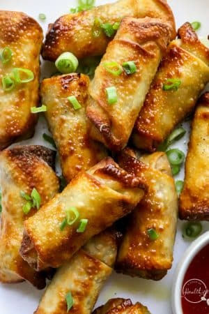 air fryer egg rolls with dipping sauce on white plate