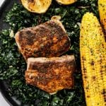 blackened mahi mahi on a plate with kale and grilled corn on the cob