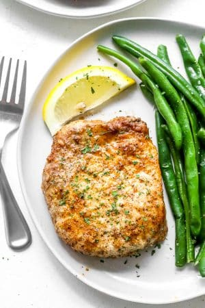 air fryer pork chops on a white plate with green beans and a lemon slice