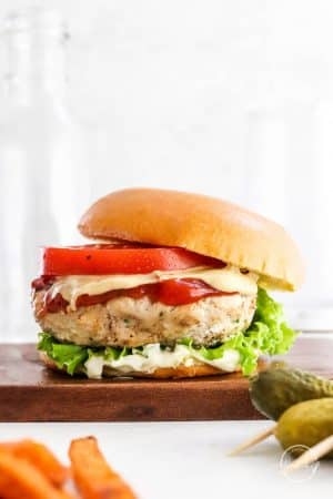 grilled turkey burger on a wood cutting board with bun, tomato, lettuce, ketchup and mayo