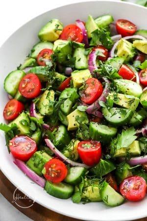 Closeup of tomato cucumber avocado salad in white serving bowl