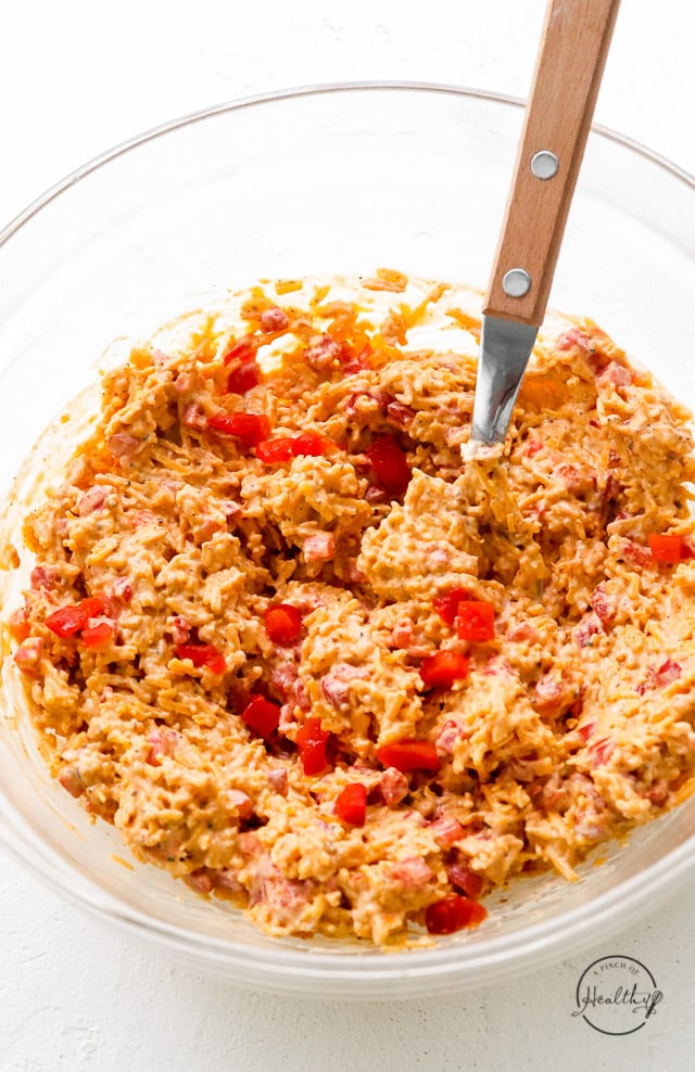 closeup pimento cheese being mixed in clear glass mixing bowl