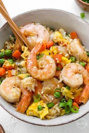 closeup of shrimp fried rice in bowl with chopsticks