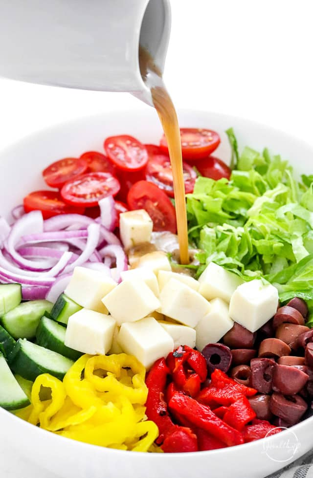 pouring dressing on Italian chopped salad
