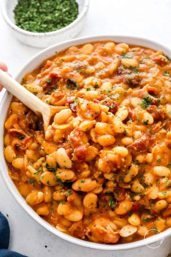 Baked beans in a white serving bowl with spoon