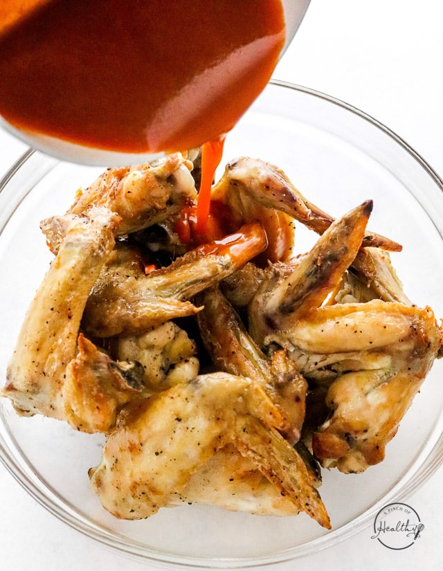 pouring buffalo sauce onto air fryer chicken wings