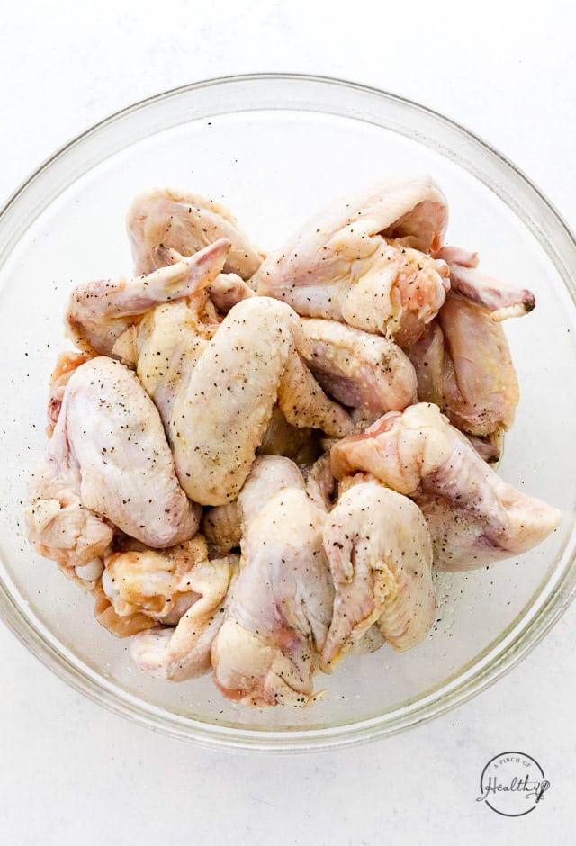 seasoned raw chicken wings in clear glass bowl