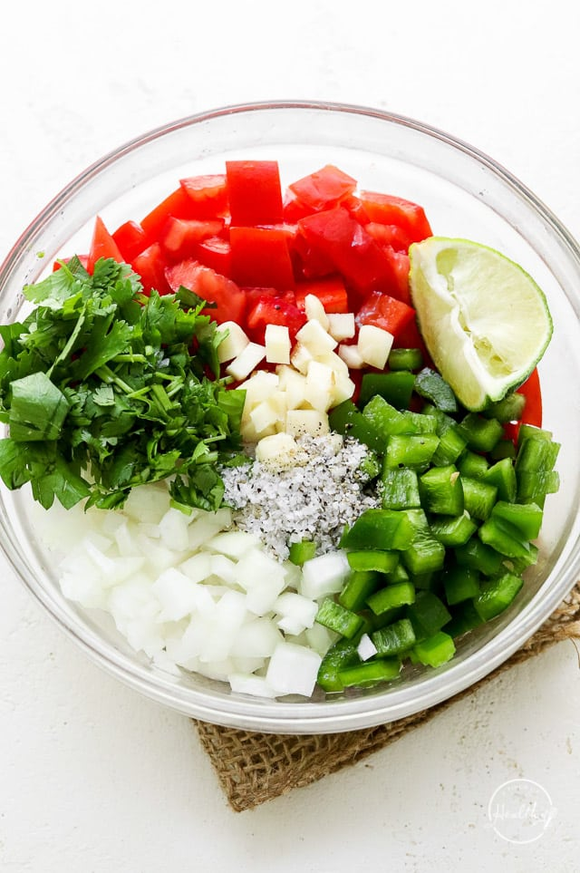 veggie and seasoning ingredient piles in a clear glass bowl