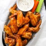 Air fryer buffalo wings in a serving dish with ranch, celery and carrot