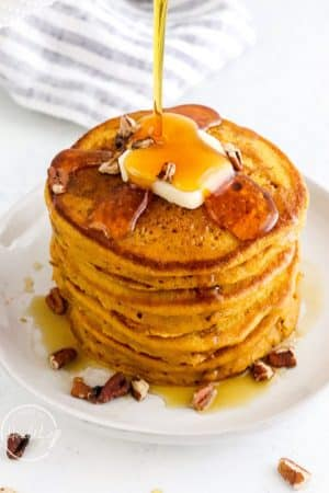pumpkin pancakes with a pat of butter getting maple syrup poured on top